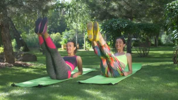 Aktivní fitness žen ve sportovní sedů ab s nohama na cvičení rohože v letním parku, rozvíjet sílu v horní břišní svaly. Sportovní žen dělá sit-up cvičení venku.