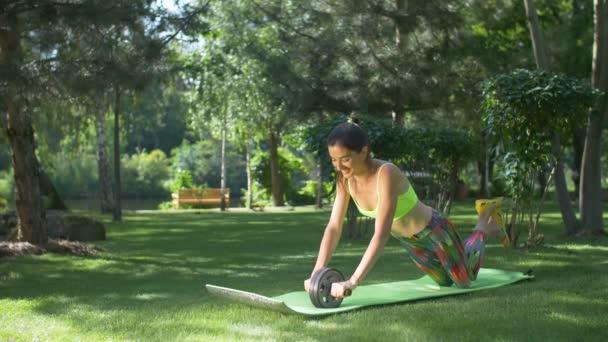 S úsměvem fit žena cvičit s ab roller v parku
