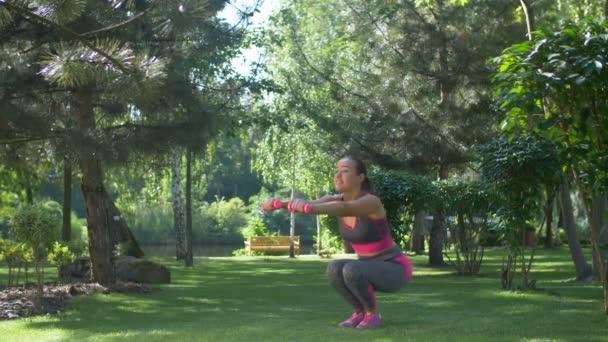 Fitness žena s činkami venku v podřepu