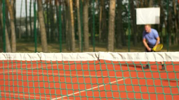 Rozmazané tenista bít předák v tenise čisté. Zaměřit se na tenisové sítě. Aktivní sportovní muž chybí výstřel a míč bít v síti při hraní tenisu hru na tvrdém povrchu. Zpomalený pohyb.