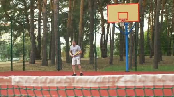 Zdravého životního stylu sportovní muž hrát tenis venkovní