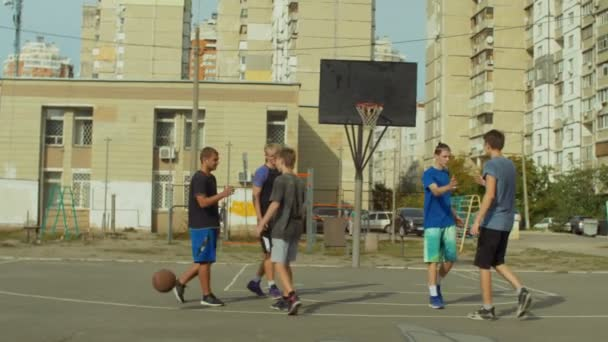Teenage basketball players shaking hands after match