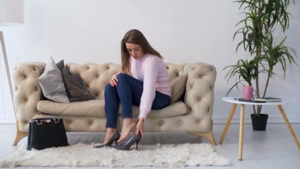 Žena masíruje nohy po nošení bot na podpatku