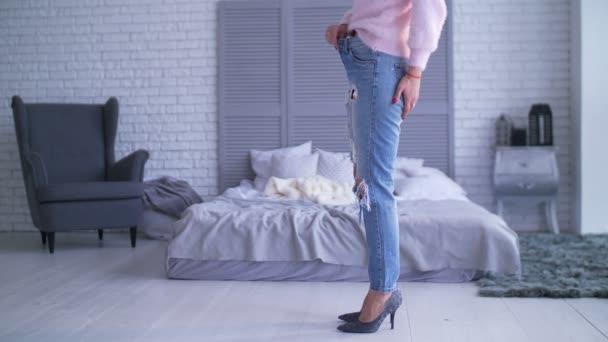 Žena ukazuje její weightloss tím, že nosí staré džíny