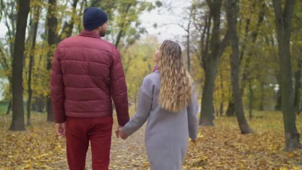 Romantic couple walking togehter through autumn park