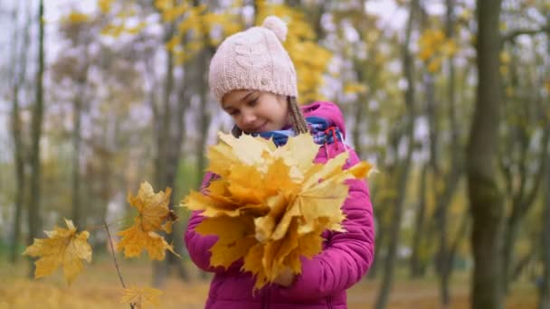 Portrait of kid holding bouquet of autumn foliage