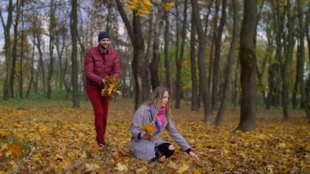 Carefree joyful couple relaxing in autumn park