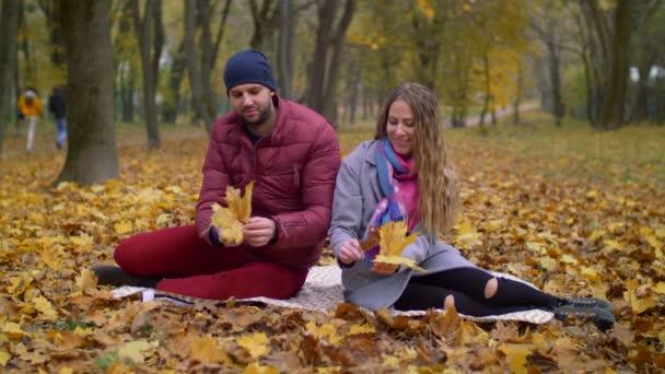 Positive romantic couple relaxing in autumn park