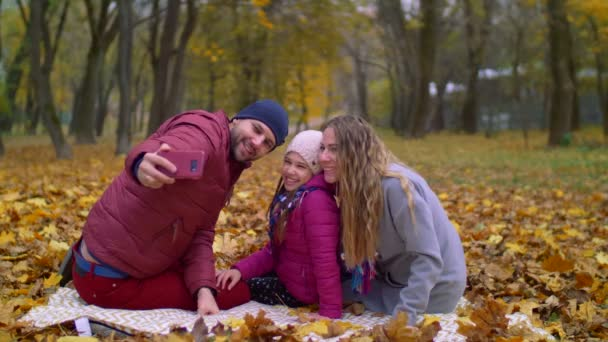 Positive family taking selfie on cellphone in autumn