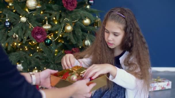 Kleines Mädchen helfen schmücken den Weihnachtsbaum