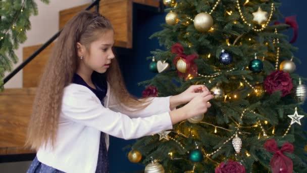 Niedliche Mädchen schmücken Weihnachtsbaum mit bunten Tand