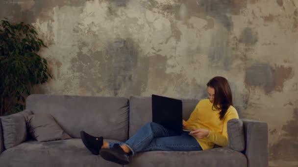 Agyonhajszolt nő szundikált a kanapén laptop