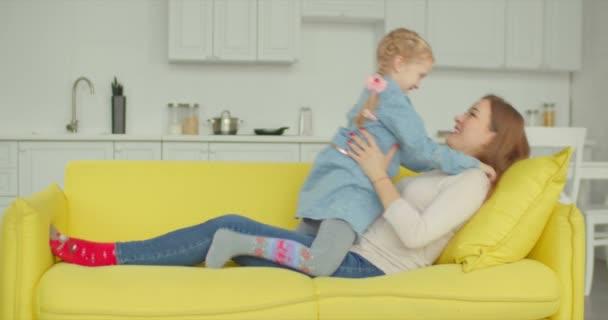 Sorglos Mutter und Tochter haben Spaß auf dem Sofa