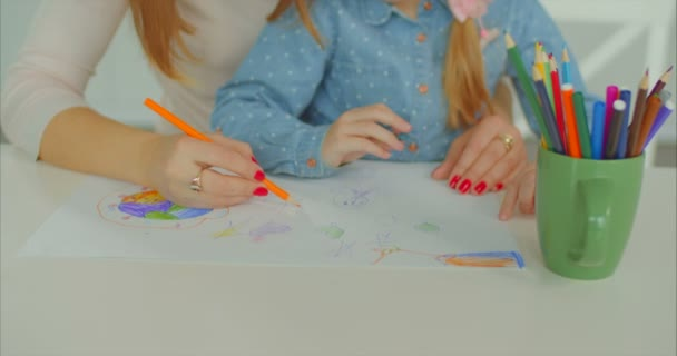 Hands of mother and kid creating artwork at desk