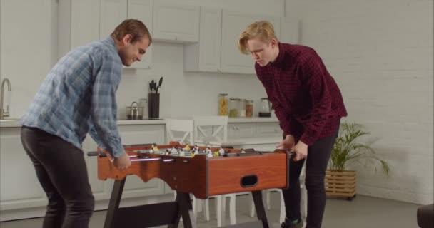 Joyful guys playing foosball in loft apartment