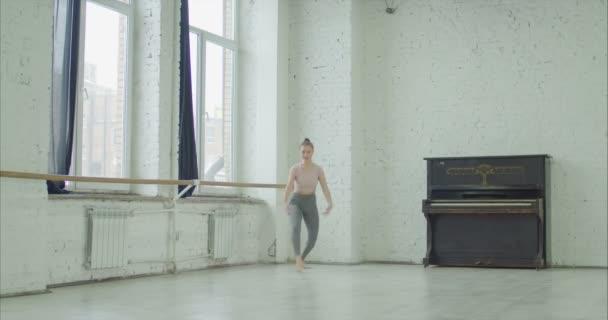 Ballet dancer performing grand jete in dance studio