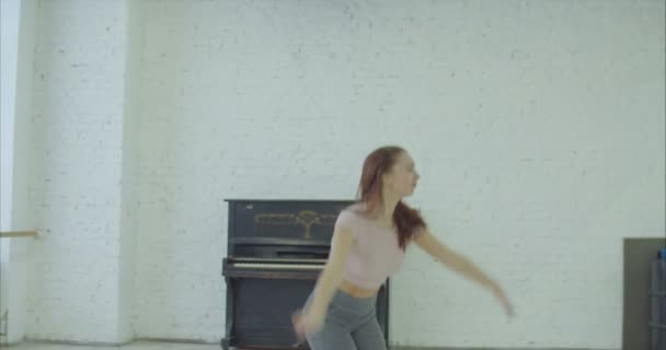 verrückte ausdrucksstarke Tänzerin mit glatten, fliegenden braunen Haaren, die völlig in modernen Tanz vertieft ist, leidenschaftliche Tanzbewegungen ausführt und während der Probe im Tanzstudio emotional Klavier spielt.