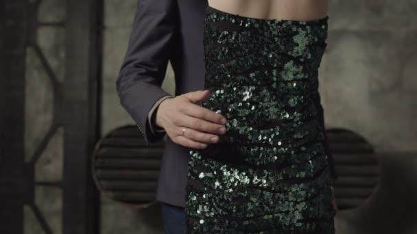 A magabiztos ember a hivatalos viselet gazdaság nő a kezét a womans hát alsó derék körül midsection. Közeli kép a férfi kezét, átfogó bájos womans Karcsú derék öltözött elegáns koktél ruha