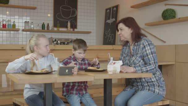Chůva zakazující dětem herní telefony v kavárně