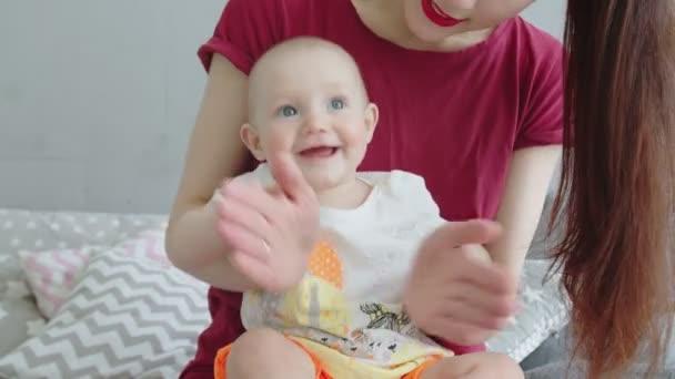 Radostné miminko hrající v dlaních s matkou doma
