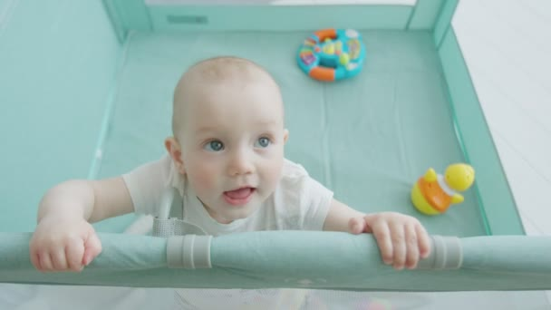 Infant girl standing holding on to edge of playpen