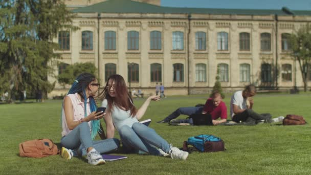 Two female college friends gossiping on campus lawn