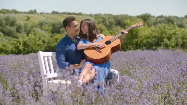 Excited couple with guitar resting in floral glade