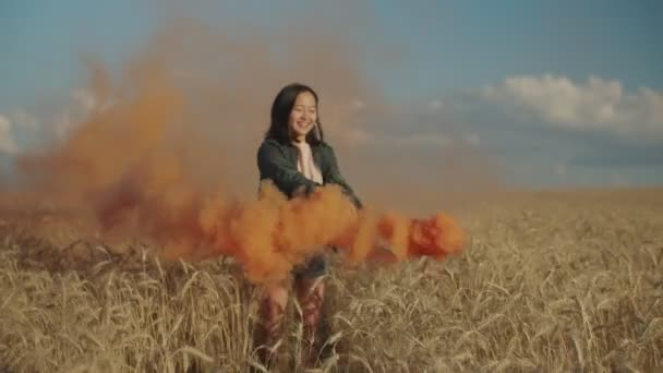 Radostná asijská žena s barevnou kouřovou bombou venku