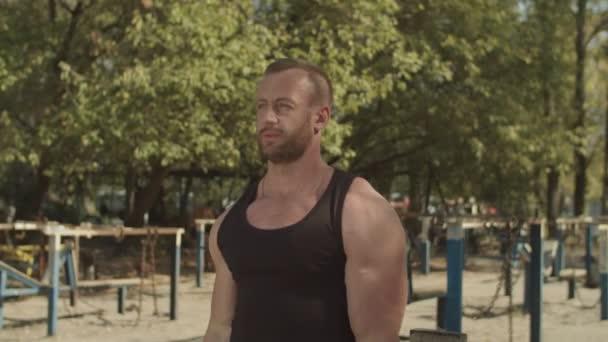 Starker Bodybuilder mit Langhantel Bizeps Locken