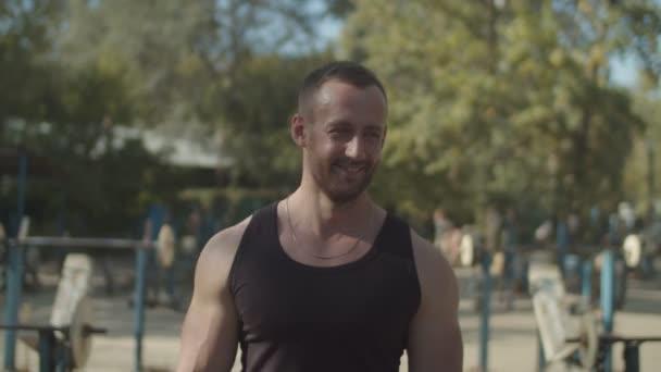 Lächelnder Bodybuilder zu Fuß in Outdoor-Fitness-Studio