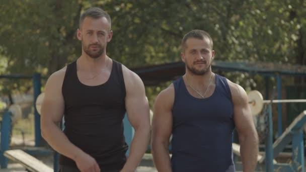 Positive Bodybuilder mit im Freien gekreuzten Armen