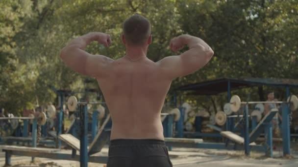 Shirtless stromg man beugt Muskeln im Freien