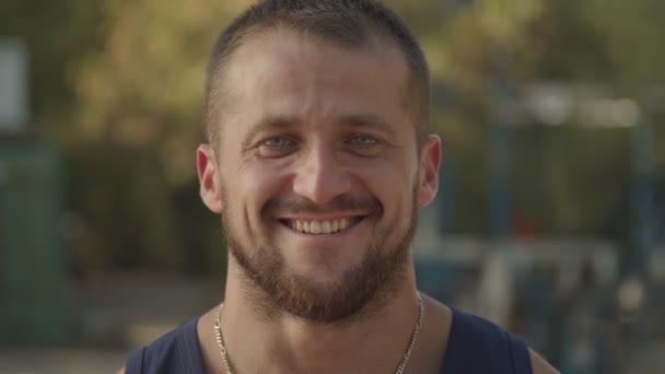 Porträt eines lächelnden bärtigen Sportlers im Freien