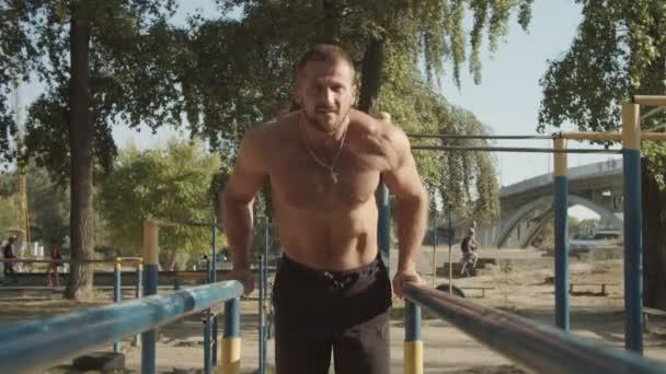 Hemdloser Mann tut Trizeps Dips auf parallelen Bars