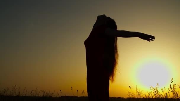 Bezstarostná žena těší svobodu v přírodě při západu slunce
