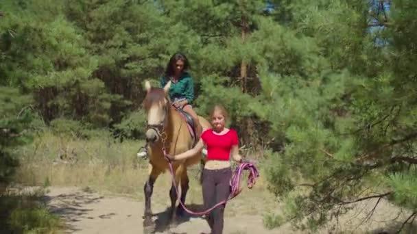 Junge Ausbilderin reitet Frau auf Pferd in der Natur