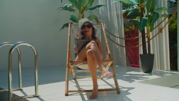 Pozitivní uvolněná žena mluví po telefonu u bazénu