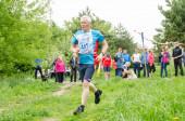 starší muž běží na trati na závodním závodě mezi vyššími