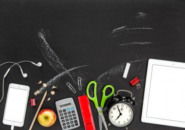 Back to school. Office supplies and digital gadgets on black chalkboard background: