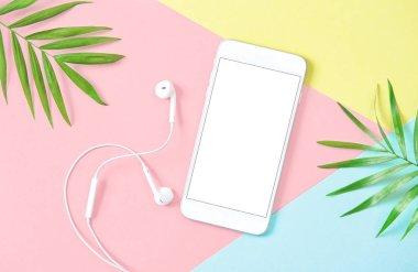 Mobile phone headphones flat lay background green leaves