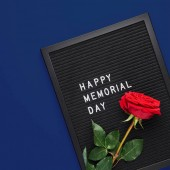 Black letterboard with white plastic letters with quote Happy Memorial Day, and rose on navy blue background. Square crop.