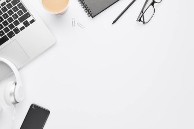 Work space concept. Top view of laptop, white headphones, black cell phone, notebook, glasses and coffee on white background with copy space. Flat lay stock vector
