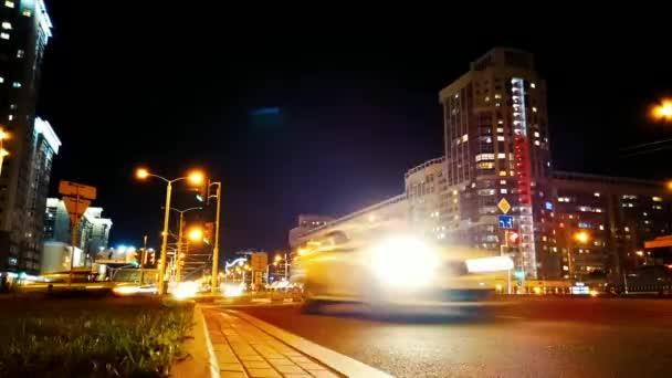 Time lapse Minsk city crossroad Derzhinsky avenue slavný Malinovka okres boční pohled HD. Večer světlomety aut. Auta jezdí a odbočují na křižovatce Moskevského okresu Minsk.