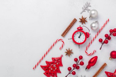 Christmas composition with alarm clock, souvenirs, candy cane, holly on stone background. Xmas holiday 2021 celebration. Flat lay, copy space - Image