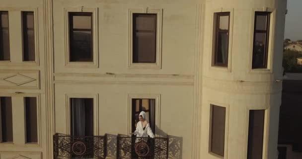 Szexi lány fehér köntösben áll az erkélyen a szálloda