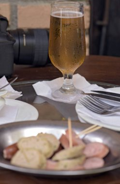 Glass of beer in popular bar with sausage platter ahead in Brazil