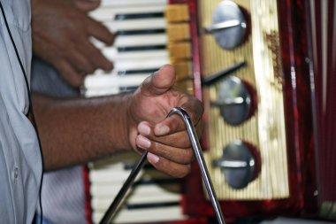 Closeup of triangle player, typical of the Brazilian Northeastern music trios. Sao Paulo Brazil