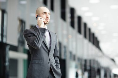 Serious young businessman in formalwear talking by smartphone while standing in modern airport lounge
