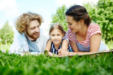 Young father and mother looking at their daughter while enjoying leisure on green lawn
