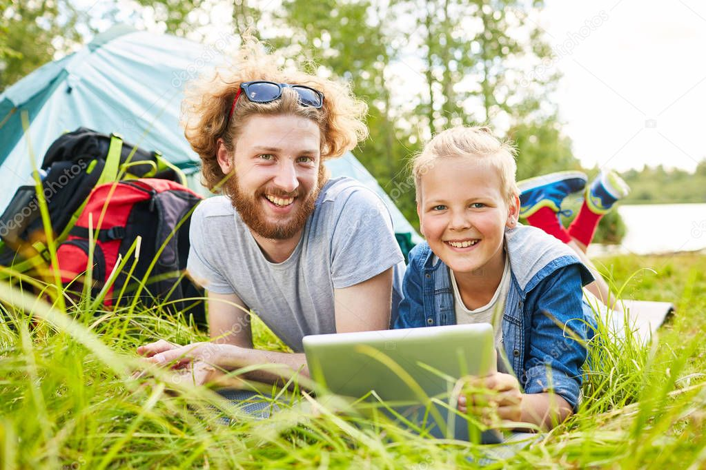 Happy brothers with touchpad relaxing on grass in the morning during their forest trip